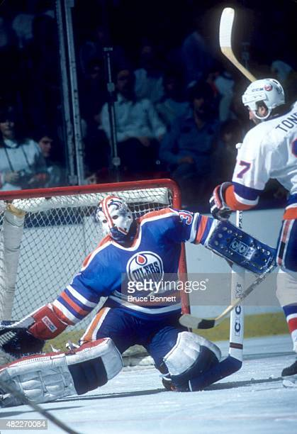 Goalie Grant Fuhr of the New York Islanders looks to make the save on as John Tonelli of the New York Islanders goes for a rebound during an NHL game...
