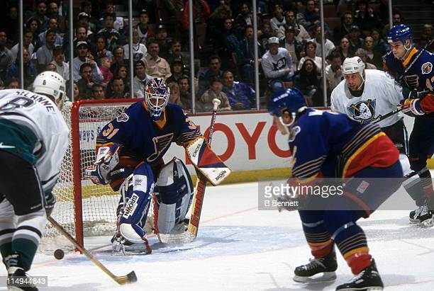 Goalie Grant Fuhr of the St. Louis Blues defends the net as his teammates Marc Bergevin and Libor Zabransky defend against Teemu Selanne and Warren...