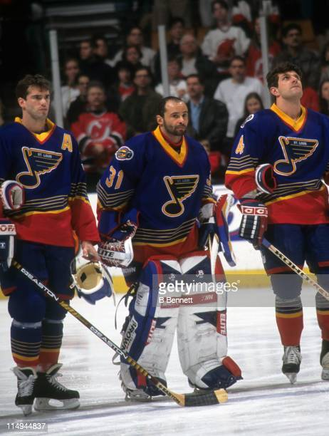 Goalie Grant Fuhr of the St. Louis Blues stands between teammates Pierre Turgeon and Marc Bergevin during the national anthem before their game...