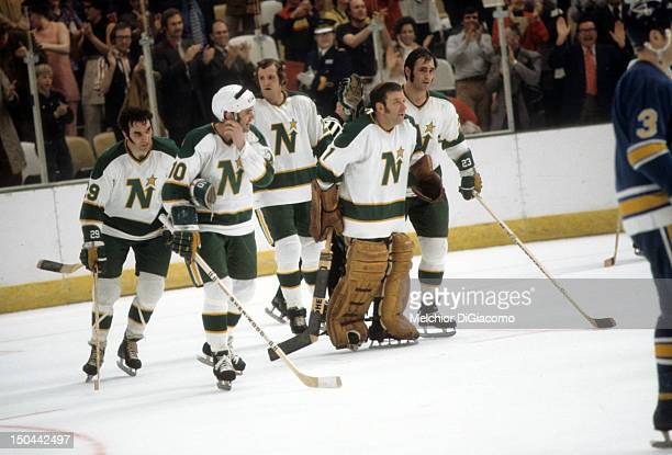 Goalie Gump Worsley of the Minnesota North Stars celebrates with teammates Lou Nanne, Dean Prentice, Murray Oliver and Tom Reid after defeating the...