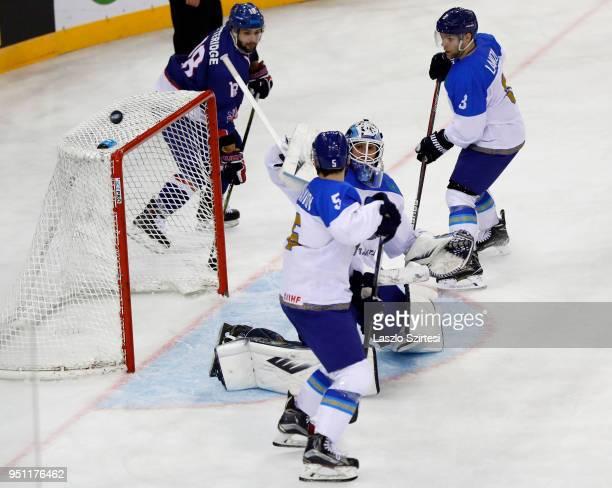 Goalie Henrik Karlsson of Kazakhstan watches the puck among Oliver Betteridge of Great Britain, Leonid Metalnikov of Kazakhstan and Artemi Lakiza of...