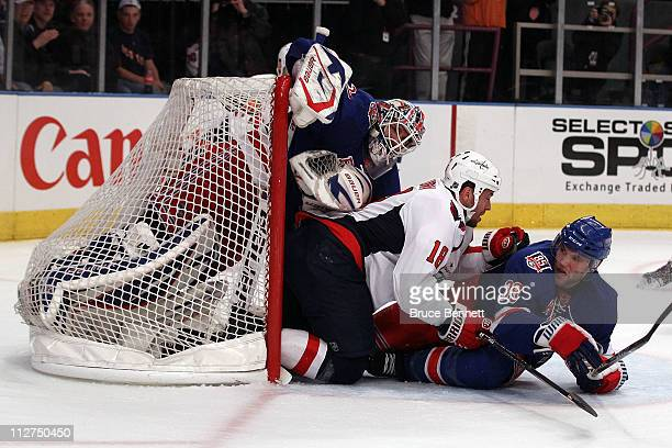 Goalie Henrik Lundqvist of the New York Rangers is pushed into the net by Marco Sturm of the Washington Capitals and Michael Sauer of the Rangers in...