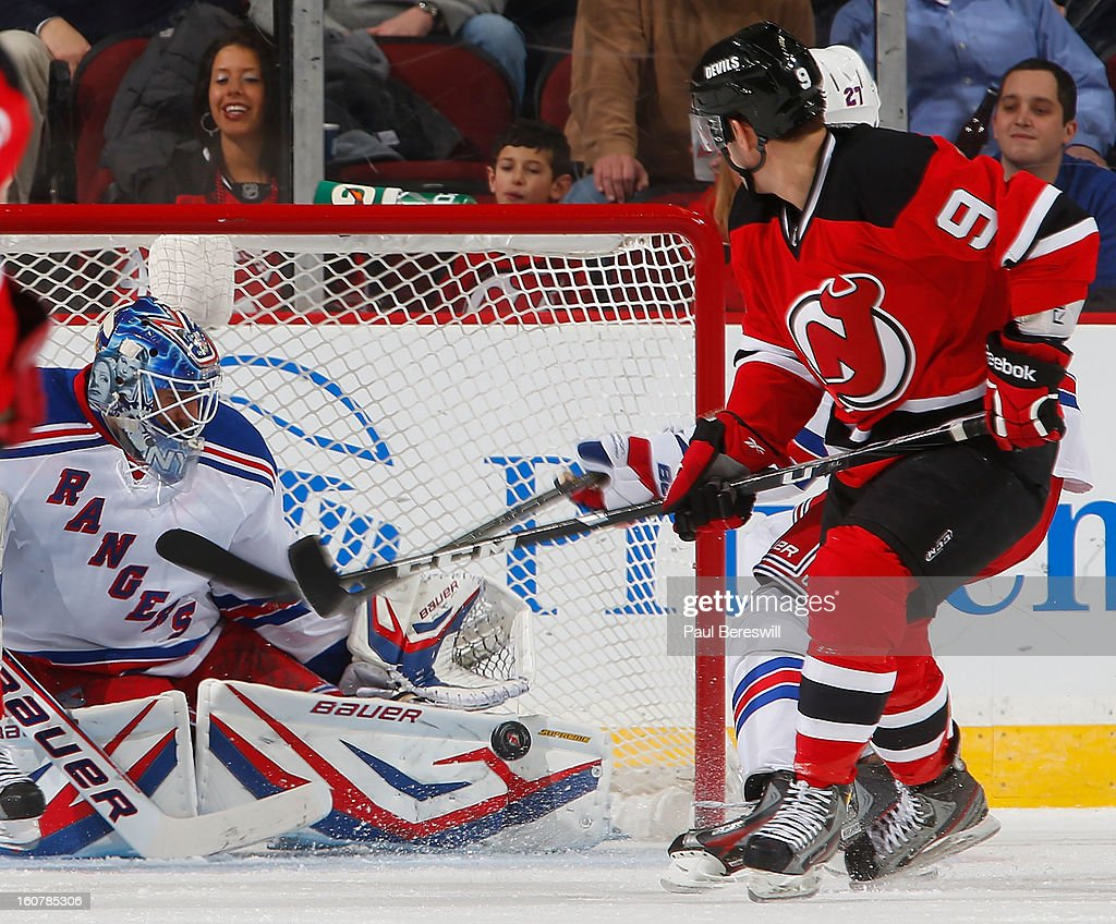 Goalie Henrik Lundqvist #30 of the New York Rangers stops a shot by Bobby Butler #9 of the New Jersey Devils during the third period of an NHL hockey game at Prudential Center on February 5, 2013 in Newark, New Jersey.