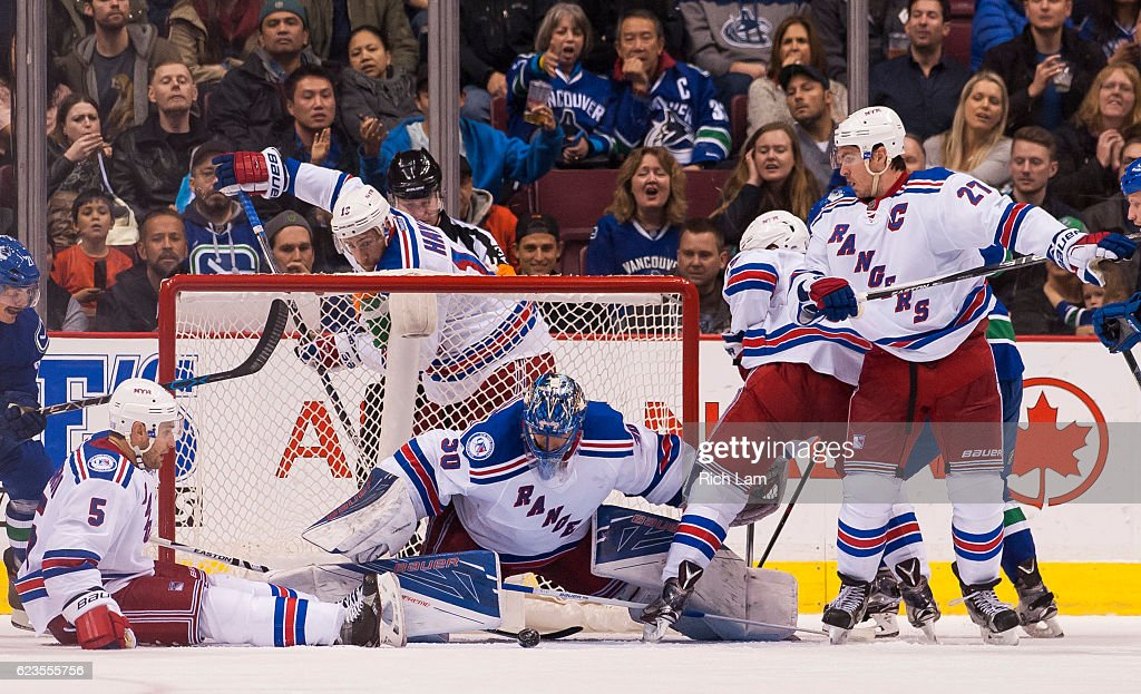Goalie Henrik Lundqvist #30 of the New York Rangers tries to cover the puck while teammates Dan Girardi #5, Ryan McDonagh #27, Kevin Hayes #13 and Jesper Fast #19 help defend during the third period in NHL action against the Vancouver Canucks on November 15, 2016 at Rogers Arena in Vancouver, British Columbia, Canada.