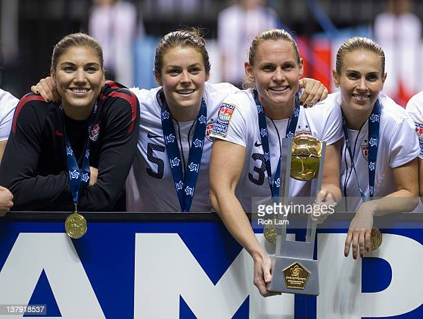 Goalie Hope Solo Kelley O'Hara Christie Rampone and Heather Mitts of the United States pose for a photo after defeating Canada in the championship...