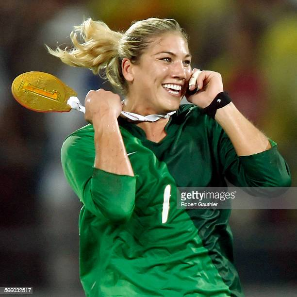 USA goalie Hope Solo runs across the field sporting a homemade gold medal while talking on a mobile phone during a post–game celebration after...
