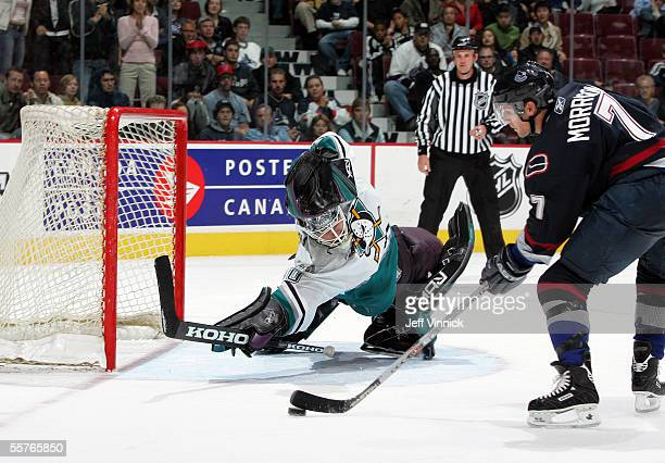 Goalie Ilya Bryzgalov of the Mighty Ducks of Anaheim dives across the crease as center Brendan Morrison of the Vancouver Canuck mishandles the puck...