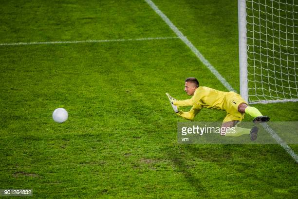 goalie in mid-air defending goal - goalie goalkeeper football soccer keeper stock pictures, royalty-free photos & images