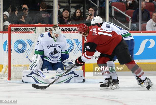 Goalie Jacob Markstrom of the Vancouver Canucks deflects the puck away from the net on the shot by Christian Dvorak of the Arizona Coyotes as Michael...