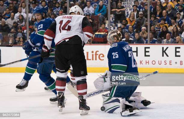 Goalie Jacob Markstrom of the Vancouver Canucks makes a save while Richard Panik of the Arizona Coyotes looks for a rebound in NHL action on April...