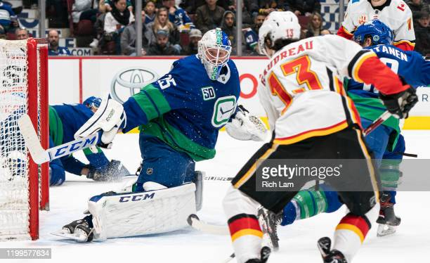 Goalie Jacob Markstrom of the Vancouver Canucks slides over to stop Johnny Gaudreau of the Calgary Flames in close during NHL action at Rogers Arena...