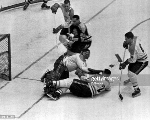 Goalie Jacques Plante and teammate Doug Harvey of the Montreal Canadiens block a shot by Willie O'Ree of the Boston Bruins as Canadiens JC Tremblay...