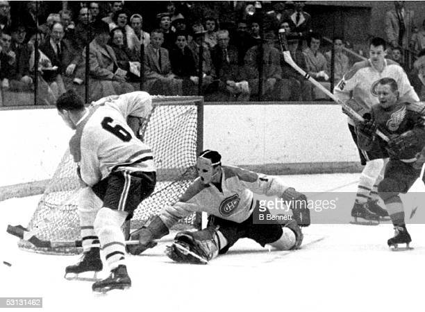 Goalie Jacques Plante makes the save as his teammate Ralph Backstrom skates around the net with the rebound during an NHL game against the Detroit...