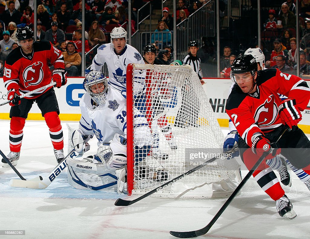Goalie James Reimer #34 of the Toronto Maple Leafs protects the net during the second period as Marek Zidlicky #2 of the New Jersey Devils circles with the puck at an NHL hockey game at Prudential Center on April 6, 2013 in Newark, New Jersey. The Leafs won 2-1.
