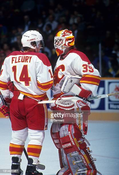 Goalie Jeff Reese and Theoren Fleury of the Calgary Flames talk during an NHL game in November, 1992 at the Olympic Saddledome in Calgary, Alberta,...