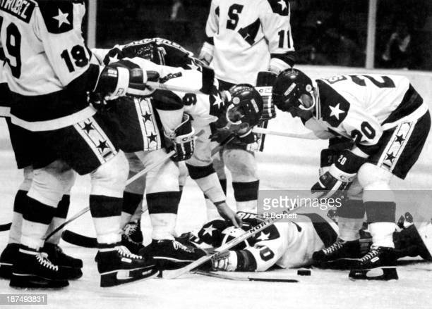 Goalie Jim Craig of the United States is checked by teammates Bill Baker and Bob Suter after being hit in the neck during warmups before their game...