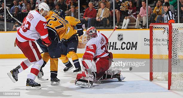 Goalie Jimmy Howard and Brad Stuart of the Detroit Red Wings let a shot by Shea Weber of the Nashville Predators find the back of the net during an...