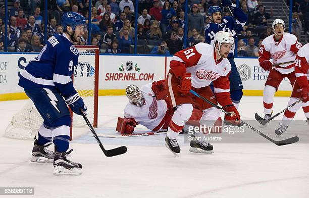Goalie Jimmy Howard and Xavier Ouellet of the Detroit Red Wings skates against Tyler Johnson of the Tampa Bay Lightning at Amalie Arena on December...