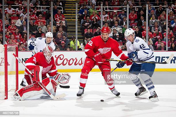 Goalie Jimmy Howard of the Detroit Red Wings makes a save as teammate Jonathan Ericsson ties up Tyler Bozak of the Toronto Maple Leafs in front of...