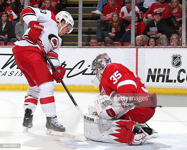 Goalie Jimmy Howard of the Detroit Red Wings makes a save on Jeff Skinner of the Carolina Hurricanes during an NHL game on April 11 2014 at Joe Louis...