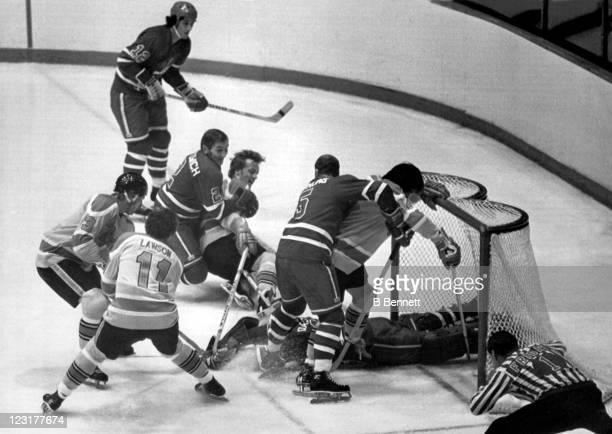 Goalie Joe Daley of the Winnipeg Jets dives on the puck as Bryan Campbell Danny Lawson Paul Terbenche and Pat Price of the Vancouver Blazers tried to...
