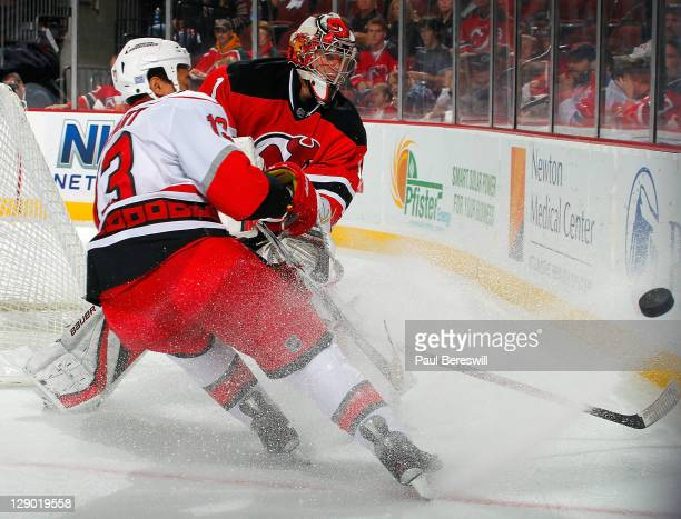 Goalie Johan Hedberg of the New Jersey Devils clears the puck from Anthony Stewart of the Carolina Hurricanes during the first period of an NHL...