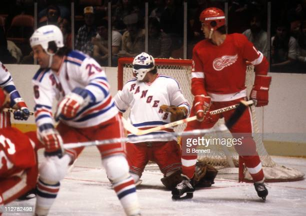 Goalie John Davidson of the New York Rangers follows the puck as his teammate Dave Maloney looks to defend while Mike Foligno of the Detroit Red...