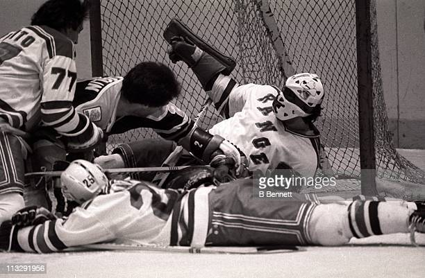 Goalie John Davidson of the New York Rangers is dog piled by teammates Phil Esposito and Mario Marois and Lee Fogolin of the Edmonton Oilers on...
