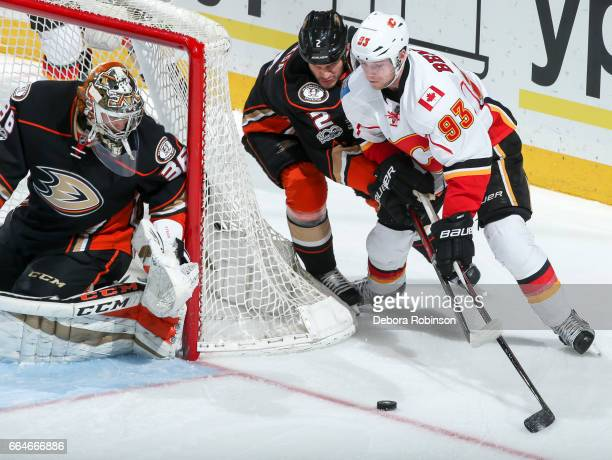 Goalie John Gibson and Kevin Bieksa of the Anaheim Ducks defend against Sam Bennett of the Calgary Flames as he brings the puck around the net during...