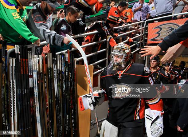 Goalie John Gibson of the Anaheim Ducks and fans high five as the Ducks take the ice before the game against the Calgary Flames at Honda Center on...