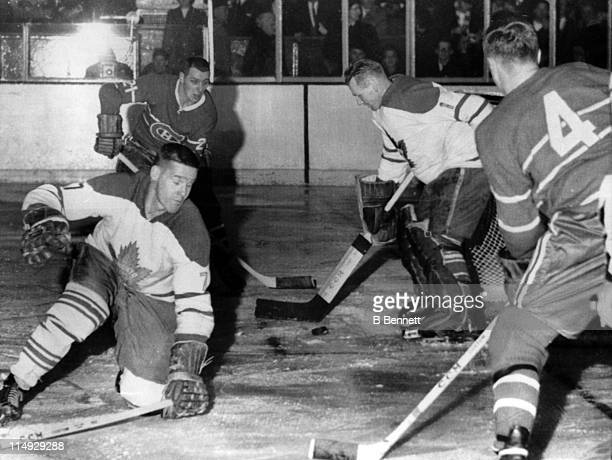 Goalie Johnny Bower and Tim Horton of the Toronto Maple Leafs try to block the puck as Jean Beliveau and Gilles Tremblay of the Montreal Canadiens...