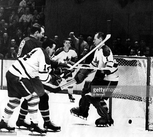 Goalie Johnny Bower of the Toronto Maple Leafs can't stop the puck as his teammate Dave Keon looks to block out Bob Nevin of the New York Rangers on...