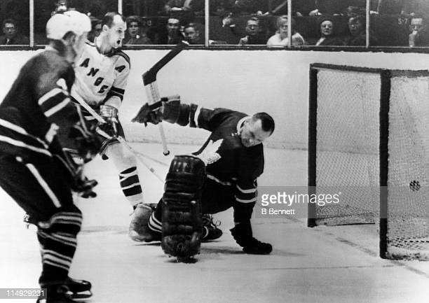 Goalie Johnny Bower of the Toronto Maple Leafs is scored on by Jean Ratelle of the New York Rangers as Don Marshall of the Rangers and Red Kelly of...