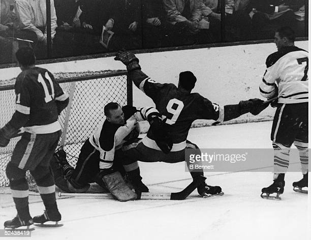 Goalie Johnny Bower of the Toronto Maple Leafs makes the save as Gordie Howe of the Detroit Red Wings slides into him circa 1960's at the Detroit...