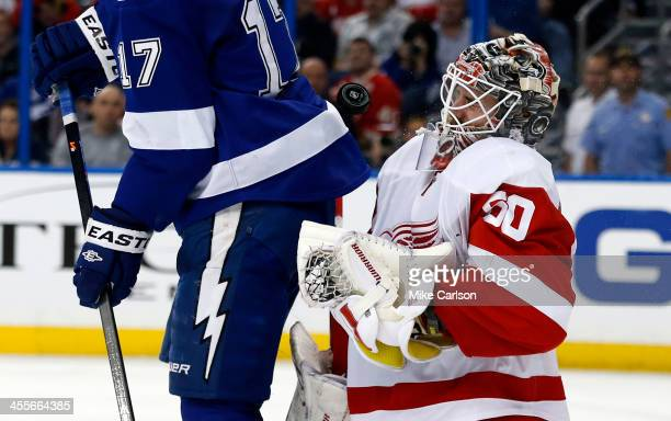 Goalie Jonas Gustavsson of the Detroit Red Wings takes a puck off the face mask behind Alex Killorn of the Tampa Bay Lightning at the Tampa Bay Times...