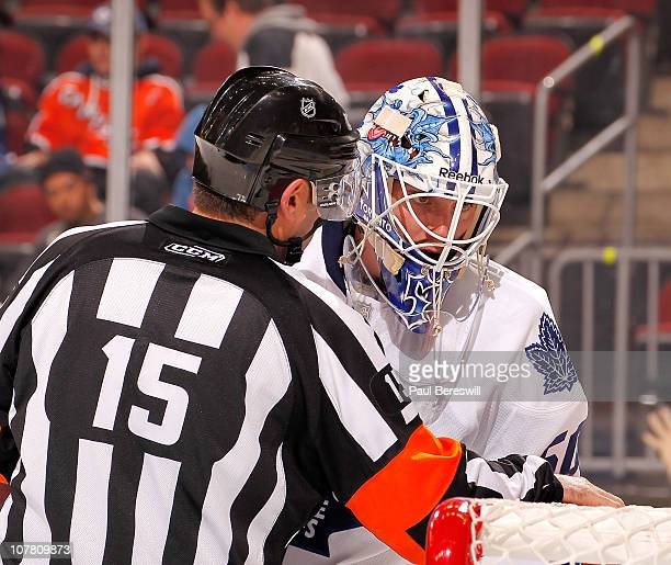 Goalie Jonas Gustavsson of the Toronto Maple Leafs is spoken to by referee Stephane Auger during a timeout in an NHL game against the New Jersey...
