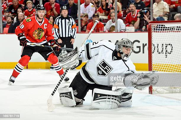 Goalie Jonathan Quick of the Los Angeles Kings catches the puck as Jonathan Toews of the Chicago Blackhawks watches in the background in Game One of...