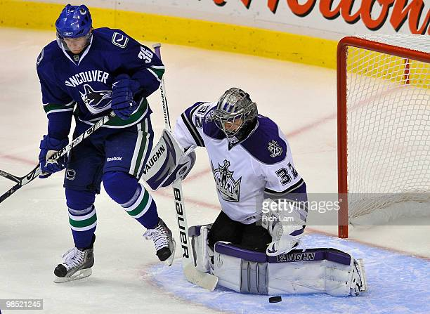 Goalie Jonathan Quick of the Los Angeles Kings makes a save while Jannik Hansen of the Vancouver Canucks tries to provided a screen for the shot...
