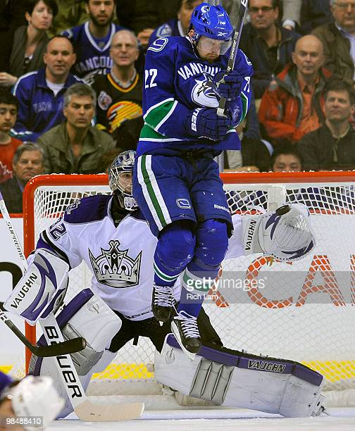 Goalie Jonathan Quick of the Los Angeles Kings reaches out to make a glove save while Daniel Sedin of the Vancouver Canucks tries to get out of the...