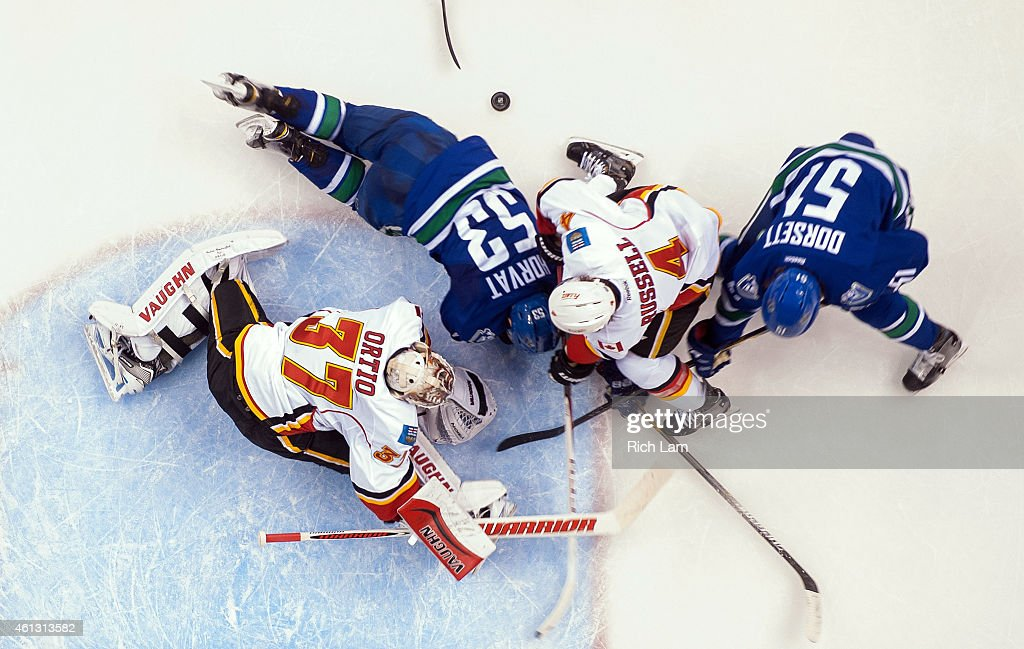 Goalie Joni Ortio #37 of the Calgary Flames scrambles to keep the puck out while Bo Horvat #53 and Derek Dorsett #51 of the Vancouver Canucks battles with Kris Russell #4 of the Calgary Flames for the loose puck during the third period in NHL action on January 10, 2015 at Rogers Arena in Vancouver, British Columbia, Canada.
