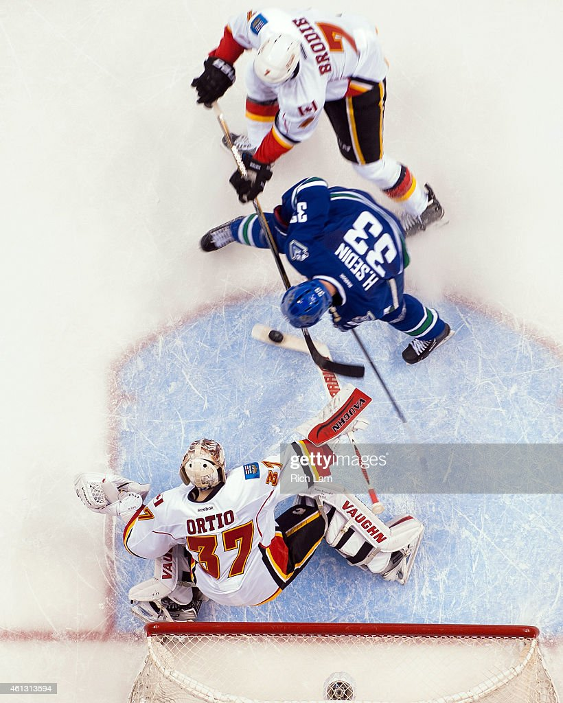 Goalie Joni Ortio #37 of the Calgary Flames stops Henrik Sedin #33 of the Vancouver Canucks in close as T.J. Brodie #7 of the Calgary Flames helps defend on the play during the third period in NHL action on January 10, 2015 at Rogers Arena in Vancouver, British Columbia, Canada.