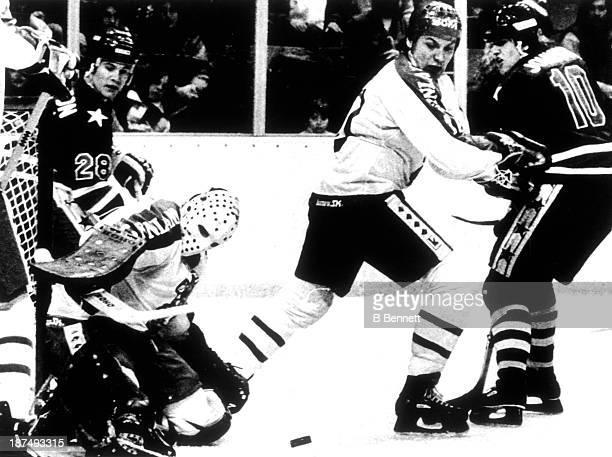 Goalie Jorma Valtonen of Finland blocks a shot by Mark Johnson of Team USA as Mikko Leinoen of Finland blocks out Johnson as John Harrington of Team...