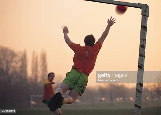 Goalie jumping for ball in soccer game
