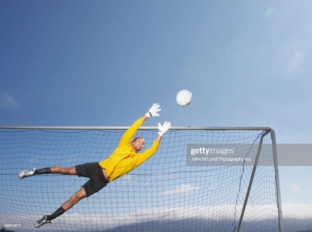 Goalie jumping to block soccer ball : Stock Photo