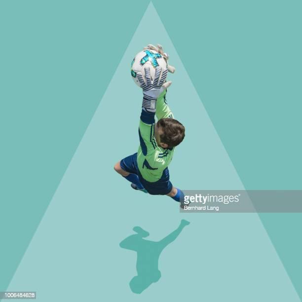 goalie jumping to catch ball, elevated view - torhüter stock-fotos und bilder