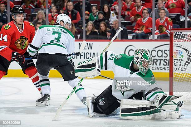 Goalie Kari Lehtonen of the Dallas Stars gloves the puck as Richard Panik of the Chicago Blackhawks and John Klingberg watch from behind in the third...