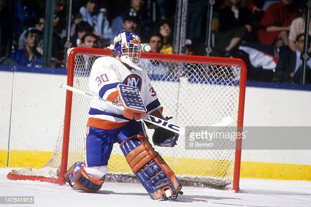 Goalie Kelly Hrudey of the New York Islanders makes the save during an NHL game circa 1987 at the Nassau Coliseum in Uniondale New York
