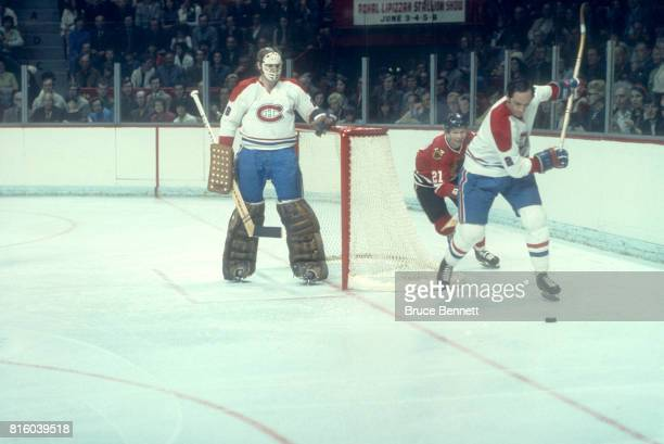 Goalie Ken Dryden of the Montreal Canadiens defends the net as his teammate Jacques Laperriere shoots the puck out of the zone as Stan Mikita of the...