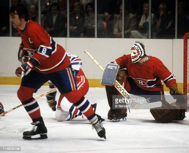 Goalie Ken Dryden of the Montreal Canadiens defends the net while his teammate Serge Savard skates up the ice during their game against the New York...