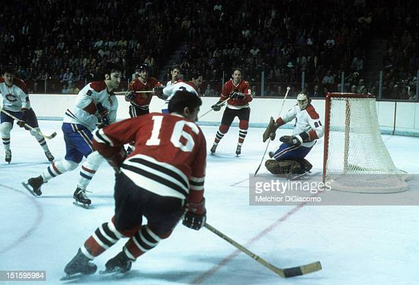 Goalie Ken Dryden of the Montreal Canadiens follows the play as Chico Maki of the Chicago Blackhawks skates with the puck during a game in the 1973...